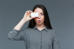 Funny woman covering eye with blank card Stock Images