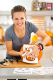 Funny woman creating pumpkin Jack-O-Lanter for Halloween party Royalty Free Stock Photography