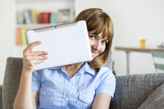 Funny woman with digital tablet in modern apartment. Playing with ipad Royalty Free Stock Photography