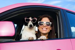 Funny woman with dog in pink car. Woman and dog in pink car on summer road trip vacation. Funny dog with sunglasses traveling. Travel with pet concept stock photos