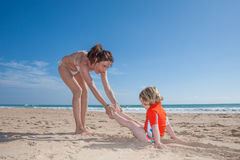 Funny woman dragging child on sand beach Stock Photos