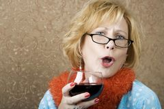 Funny Woman Drinking Wine. Extroverted woman with a funny expression drinking red wine Stock Image