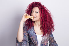 Funny woman eating a sandwich indoors. Stock Image