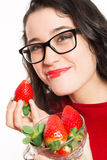 Funny woman with eyeglasses eating strawberries Royalty Free Stock Images
