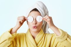 Funny woman foolishes after taking shower, wears towel and bathrobe, covers eyes with cotton wheels, going to apply cosmtics and d. O make up,  on white Stock Photos
