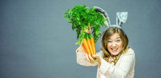 Funny woman with fresh carrot. Picture with space for your text.  royalty free stock photo