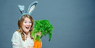 Funny woman with fresh carrot. Picture with space for your text.  stock photos