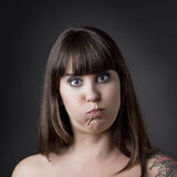 Funny woman with full cheeks. Portrait of a beautiful and funny woman with cheeks full of air against a grey background stock images