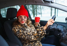 Funny woman in a fur coat and red hat talking with someone while Stock Photo