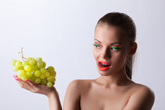 Funny woman with glow make-up and green grapes Stock Photos