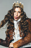 Funny woman in golden crown and leather jacket. In studio Royalty Free Stock Photo