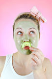 Funny woman with green facial mask and cucumber moustache. Royalty Free Stock Photos
