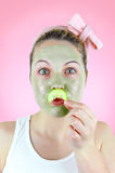 Funny woman with green facial mask and cucumber moustache. Royalty Free Stock Photography