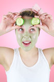 Funny woman with green facial mask and cucumber slices. Stock Photography