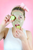 Funny woman with green facial mask eating cucumber. Stock Photos