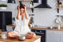 A funny woman with hair curling dressed in white bathrobe feels panic in the kitchen while cooking. A beautiful woman with hair curling dressed in white stock photo