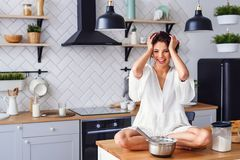 A funny woman with hair curling dressed in white bathrobe feels panic in the kitchen while cooking. A beautiful woman with hair curling dressed in white royalty free stock photography