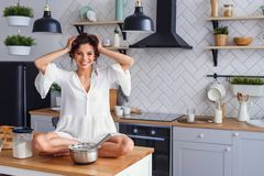A funny woman with hair curling dressed in white bathrobe feels panic in the kitchen while cooking. A beautiful woman with hair curling dressed in white stock photos