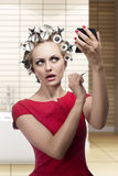 Funny woman with hair rollers. Funny portrait of blonde make-up woman wearing hair rollers, red dress and putting lipstick with brush, looking in the mirror in Stock Photography