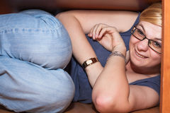 Funny woman hiding under table. Closeup of funny woman hiding under table Stock Photos