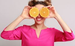 Funny woman holding halves of oranges against background stock photos