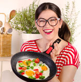 Funny woman holding pan with egg. Royalty Free Stock Photography
