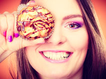 Funny woman holds cake in hand covering her eye Stock Image