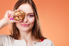Funny woman holds cake in hand covering her eye Stock Photos