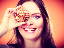 Funny woman holds cake in hand covering her eye Royalty Free Stock Image