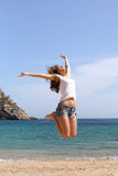Funny woman jumping on a paradise beach Stock Photos