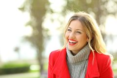 Funny woman laughing in a park in winter. Funny woman wearing a red jacket laughing outside in a park in winter Stock Photo