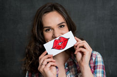 Funny Woman With Lips Sign. Beautiful Girl Holding A Sheet Of Paper With Drawn Red Lips Isolated On Gray Background royalty free stock photo