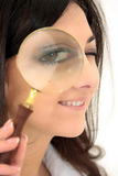 Funny woman looking through magnifier Stock Photography