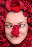Funny woman lying in petal of roses Royalty Free Stock Photography