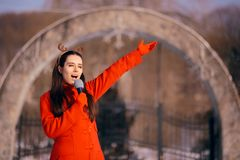 Christmas Girl Singing Carols Outdoors in Wintertime. Funny woman with microphone caroling outside on holiday season stock images