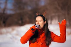 Christmas Girl Singing Carols Outdoors in Wintertime. Funny woman with microphone caroling outside on holiday season royalty free stock photos