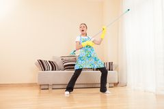 Funny woman mopping floor and playing. Beautiful girl playing music using mop Stock Photo