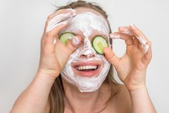 Woman with natural cream mask and cucumbers on her face. Funny woman with natural cream mask and cucumbers on her face - spa and beauty concept stock images