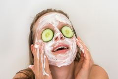 Woman with natural cream mask and cucumbers on her face. Funny woman with natural cream mask and cucumbers on her face - spa and beauty concept stock photos