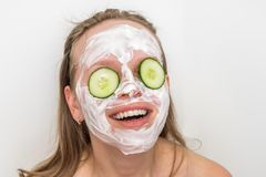 Woman with natural cream mask and cucumbers on her face. Funny woman with natural cream mask and cucumbers on her face - spa and beauty concept stock photo