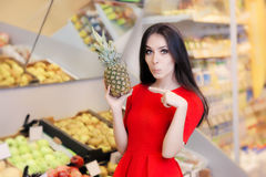Funny Woman with Pineapple Fruit in Supermarket Royalty Free Stock Images