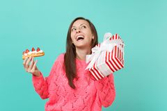 Funny woman in pink sweater looking up, hold eclair cake, red striped present box with gift ribbon isolated on blue. Background. Valentine`s, Women`s Day royalty free stock photography