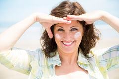 Funny woman protecting skin from sun. Funny middle aged woman applying sunscreen lotion on face on the beach Stock Photo