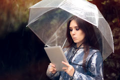 Funny Woman with Raincoat and Umbrella Holding Pc Tablet Stock Photos