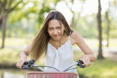funny woman riding bicycle with foliage bokeh Stock Photography