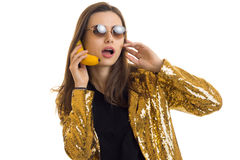 Funny woman in round sunglasses waers a golden jacket and talking in banana like a mobile phone. Isolated on white background royalty free stock images