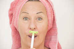 Funny woman shaving face with razor. Portrait attractive funny mature woman with towel around head, shaving her face with razor, isolated on white Royalty Free Stock Image