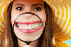 Funny woman show teeth through magnifying glass Stock Photos