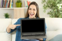 Funny woman showing a blank laptop screen at home. Funny woman showing a blank laptop screen sitting on a couch in the living room at home royalty free stock photo