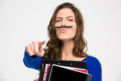 Funny woman simitating moustache with pen and pointing on camera Stock Photography
